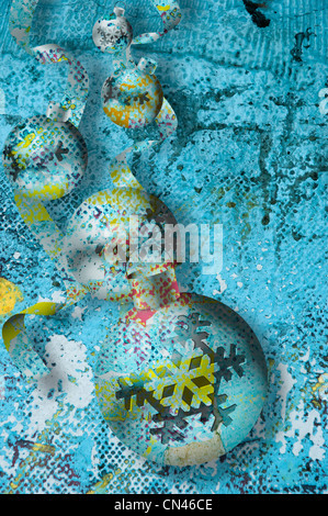 Textured Christmas ball ornaments and ribbons  float on  a decayed, distressed, turquoise background, in a surrealist - Stock Photo