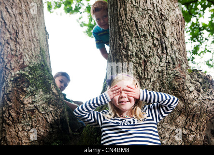 Children playing hide and seek in a woodland - Stock Photo