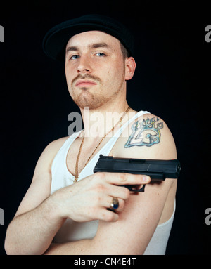 Young man holding gun, portrait - Stockfoto