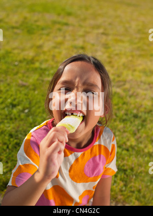 Girl biting into ice lolly, portrait - Stock Photo