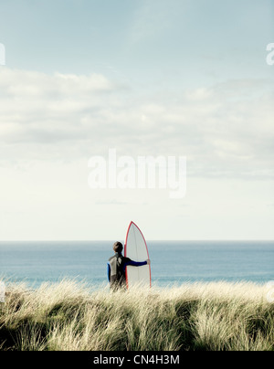 Surfer looking out to sea - Stock Photo