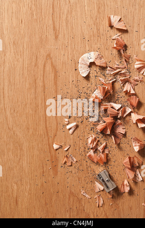 Sharpener and pencil shavings on wooden background - Stock Photo