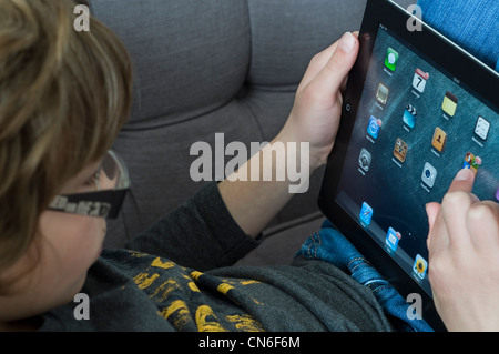 A young boy using  an iPad 2 - Stock Photo