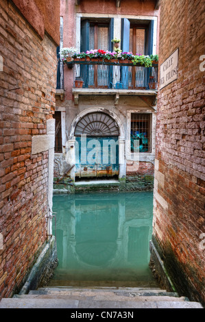 Apartment with a balcony above a canal in Venice Italy - Stock Photo