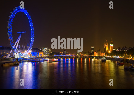 Night in London. Lights from Westminster and the London Eye reflect onto the River Thames - Stock Photo