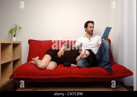 Happy young couple sitting on a sofa - Stock Photo
