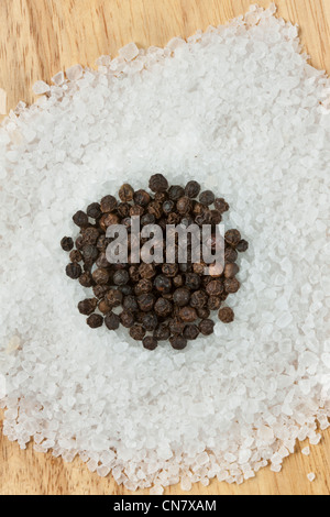 black peppercorns on top of rock salt - Stock Photo