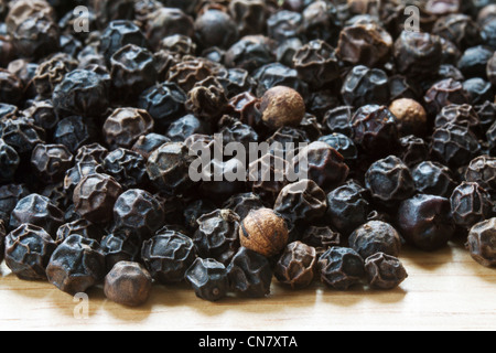 close up of black peppercorns on a wooden table - Stock Photo