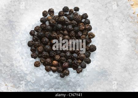 black peppercorns on top of  rock crushed salt - Stock Photo