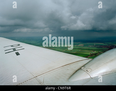 Airplane wing over rural landscape - Stock Photo