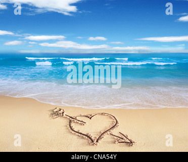 Heart with arrow, as love sign, drawn on the beach shore, with the see and sky in the background. - Stockfoto