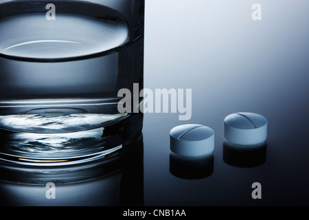 Close up of pills on reflective surface - Stock Photo