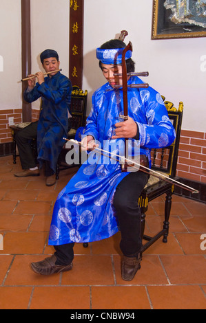 Vertical close up view of traditional Vietnamese musician playing the dan nhi or vertical violin in bright coloured - Stock Photo