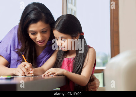 Mother teaching her daughter to write - Stock Photo