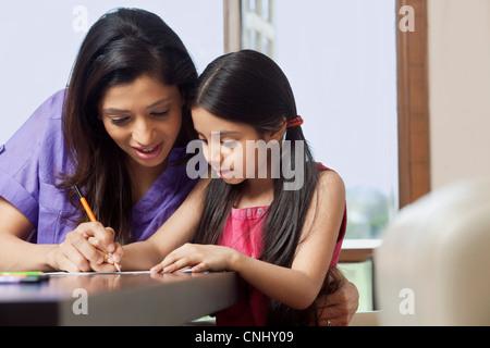 Mother teaching her daughter to write - Stockfoto