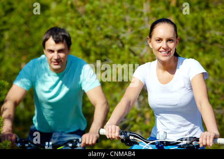 Portrait of two young people on bicycles - Stock Photo