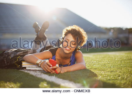 Student listening to mp3 player in grass - Stock Photo