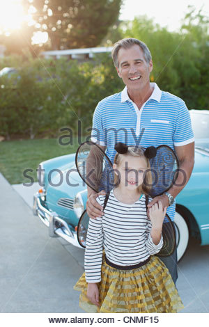 Father standing with daughter in fairy wings - Stock Photo