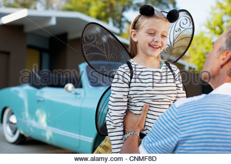 Father hugging daughter in fairy wings - Stock Photo