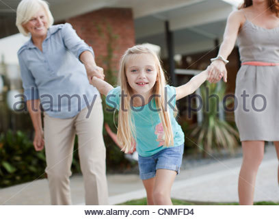Three generations of women holding hands - Stockfoto