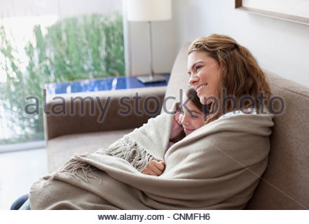 Mother and daughter wrapped in blanket on couch - Stock Photo