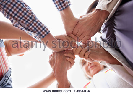 Group of hands clasped in prayer - Stock Photo