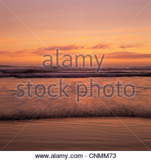 Waves rolling on beach at sunset - Stockfoto