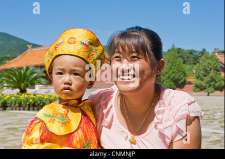 A young Chinese mother and her child dressed in traditional clothes while visiting the Eastern Qing Tombs. - Stock Photo