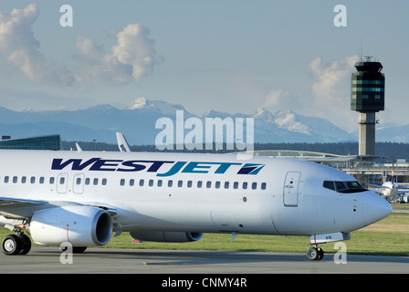 Close-up of a Westjet C-GWRG Boeing 737 (800) airliner taxiing down the runway at the Vancouver International airport. - Stock Photo