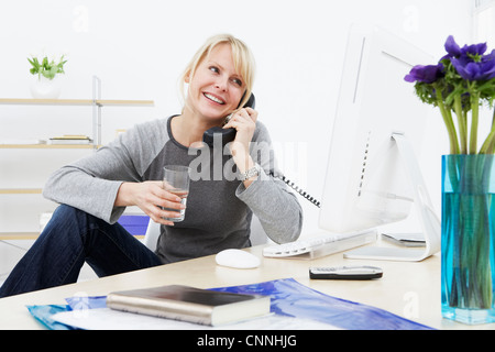 Businesswoman With Feet Up On Desk In Office Stock Photo