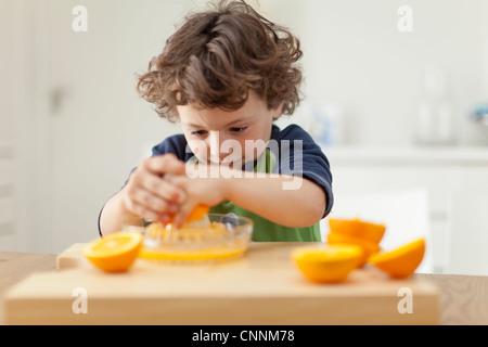 Boy squeezing oranges to make juice - Stock Photo