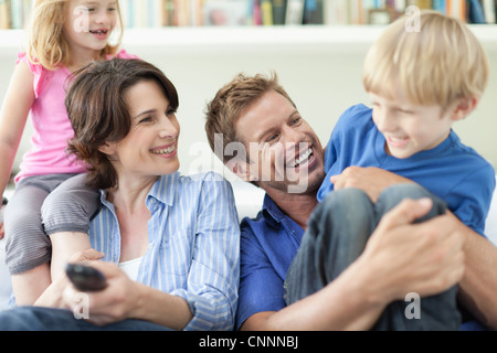 Family relaxing together on couch - Stock Photo