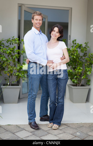 Couple smiling outside front door - Stock Photo
