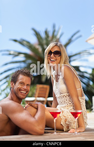 Couple relaxing by swimming pool - Stock Photo