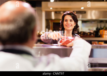 Woman buying meat from butcher - Stock Photo