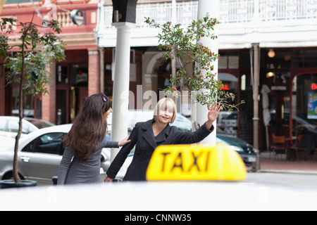 Women hailing taxi cab in city - Stock Photo