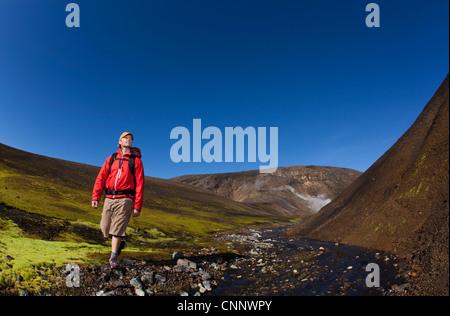 Man hiking in rocky rural creek - Stock Photo