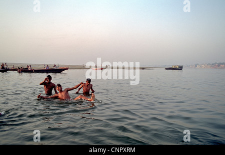 Three young indian men bathing and playing in the Ganges at the ancient Indian city of Benares (Varanasi), Uttar - Stock Photo
