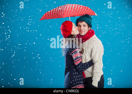 Smiling couple kissing in snow - Stock Photo