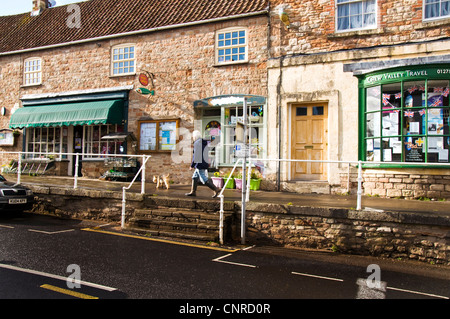 Man walking dog in Chew Magna High Street past local shops and Post Office - Stock Photo