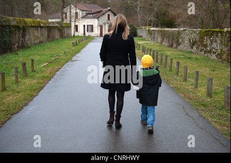Mother and son walking on path in village, holding hands, rear view - Stock Photo