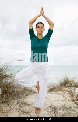 Mature woman in tree pose on beach, portrait - Stock Photo