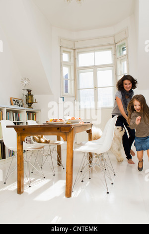 Woman playing with daughter in kitchen - Stock Photo