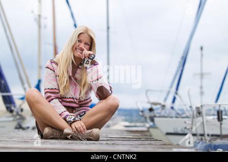 Smiling woman sitting on wooden dock - Stockfoto