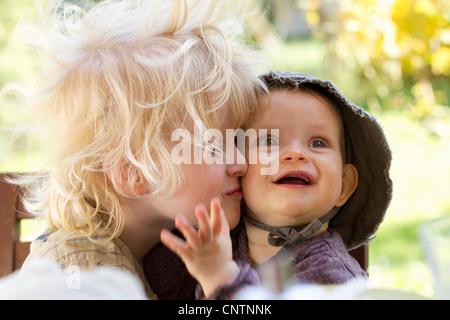 Boy kissing baby sister at table - Stock Photo