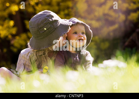 Brother holding baby sister in grass - Stock Photo