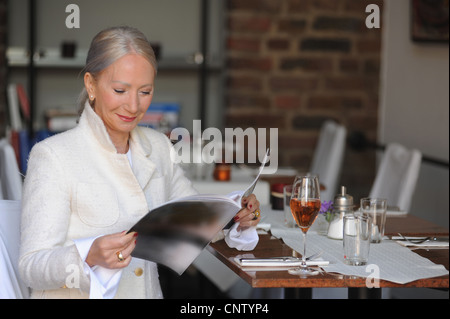 Older woman reading magazine in cafe - Stock Photo