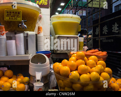 Juice stall on a street corner with oranges and carrots on display and a little fountain playing over the carrots - Stock Photo