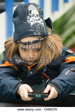 Young boy child using operating radio control toy winter hat jacket cold weather hands concentration concentrating - Stock Photo