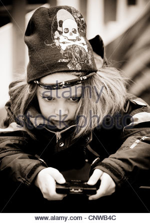 Young boy child using operating radio control toy winter jacket cold weather hands concentration concentrating pirate - Stock Photo
